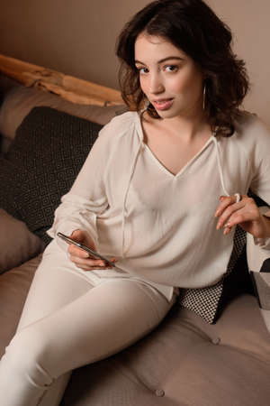Portrait of a dark-haired girl in light clothes sitting on a sofa with a phone in his hand looking at the camera.