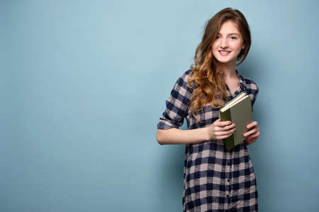 A young girl in a plaid dress stands on a blue background and holds a book in her hands and smiles at the camera.