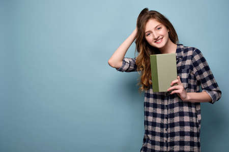 A young girl in a plaid dress stands on a blue background and holds a book in front of him, running her hand through her hair.