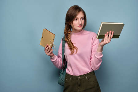 A blue-eyed girl in a pink sweater stands on a blue background with books in her hands.
