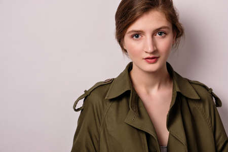 A girl in a green trench coat with collected hair stands on a light background and looks into the frame Stock Photo