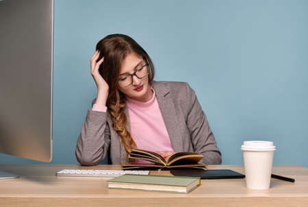 A girl in a pink sweatshirt and a gray jacket with a braid and glasses sits at a table , leaning on her hand, looks at a notebook.