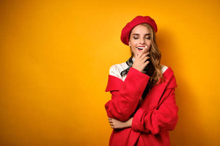 A girl with curls, red lipstick in a red coat and beret is standing on a yellow background and covers her mouth with her hand. Stock Photo