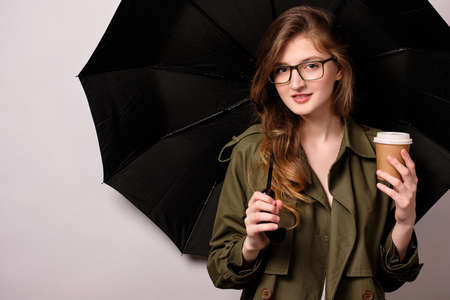 A girl is standing against the background of an opened black umbrella in a green trench coat, glasses with paper cup in her hand Stock Photo