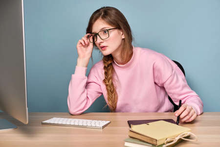 A girl in a pink sweatshirt with a braid and sits at a table and looks at the monitor adjusting his glasses. Stock Photo