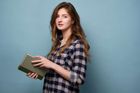A girl in a plaid shirt stands in half-turn with a book in her hands on a blue background and looks into the frame. Stock Photo