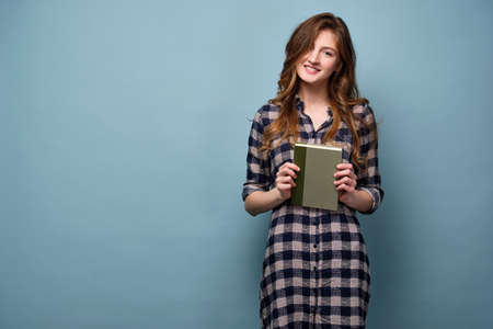 A girl in a plaid shirt stands with a book in her hands on a blue background and smiles into the frame
