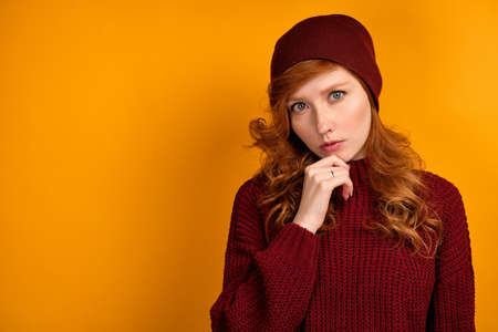 A curly red-haired girl in a burgundy sweater and hat stands on an orange background, looks into the frame holding on to her chin. Stock Photo
