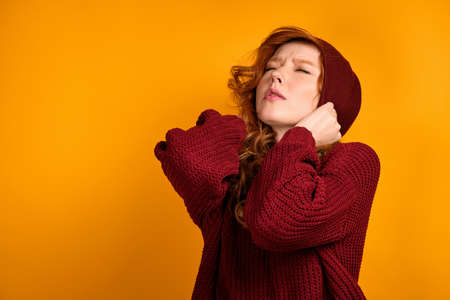 A curly red-haired girl in a burgundy sweater stands on an orange background, frowning pulls her hat down, her eyes closed.