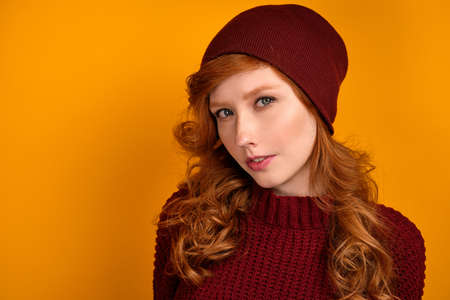 Close portrait of curly red-haired girl in a burgundy sweater and hat, standing on an orange background. Stock Photo