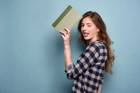 A blond-haired girl in a plaid shirt stands on a blue background with a book, sticking out her tongue and winking at the frame.