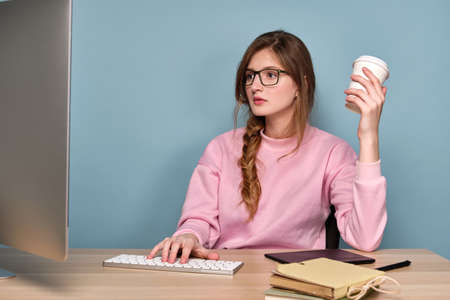 A girl with a braid in a pink sweater and glasses sits in front of a computer, looks at the monitor, with a paper cup in her hand.