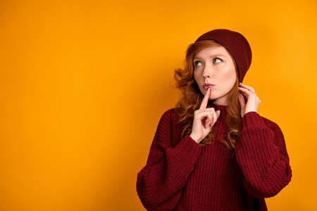 Red-haired girl in a burgundy sweater stands on an orange background and with a finger to lips, straightens her hat and looks up Stock Photo