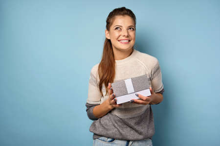 Brunette girl in a sweater stands on a blue background with a gift box in her hands and smiles into the frame. Zdjęcie Seryjne