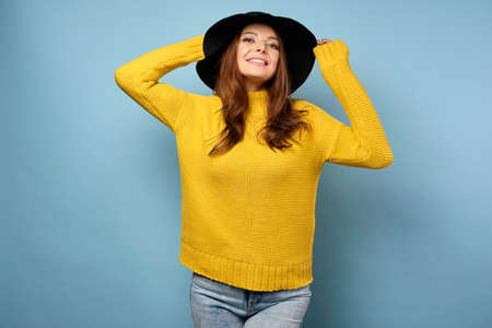 A beautiful brunette in a yellow sweater stands on a blue background, straightens her hat, throwing her head back. Zdjęcie Seryjne
