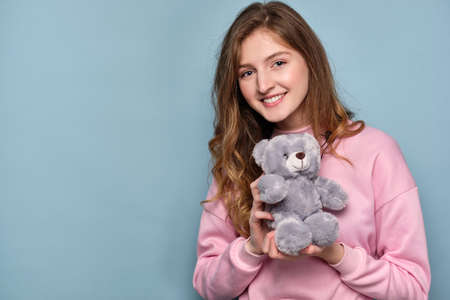 Cute girl in a pink sweatshirt a smiling frame, holding a teddy gray bear in her hands.