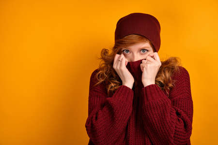 Curly red-haired girl in a burgundy sweater and hat, stands on an orange background, lifting the collar to the eyes. Stock Photo
