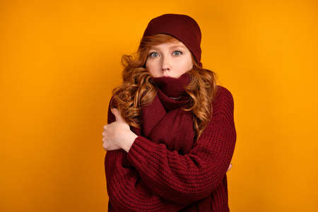 A curly red-haired girl in a burgundy sweater, scarf and hat stands embracing herself against an orange background Stock Photo