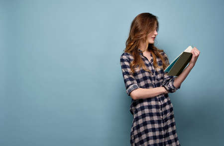 A girl in a plaid shirt stands in a half-turn on a blue background and reads a book.
