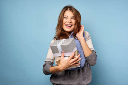 A brunette in a sweater and a blue scarf stands on a blue background, holds gift boxes in hand and smiles, looks at the top