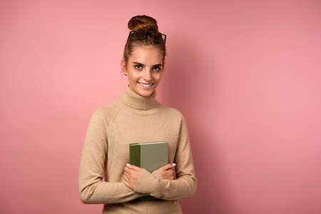 A girl in a beige turtleneck with gathered hair and glasses on her forehead stands with a book and looks in the frame. Stock Photo