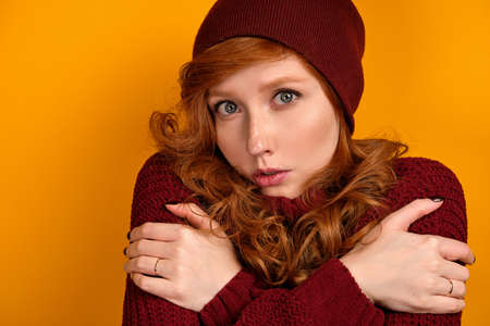 A close portrait of a red-haired girl in a burgundy sweater, scarf and hat stands embracing herself on an orange background Stock Photo