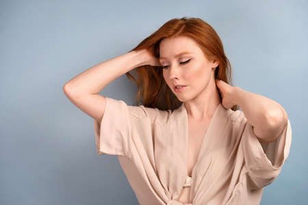 A red-haired girl in a light robe stands in half-turn on a blue background and looks upward, raising her hair. Stock Photo