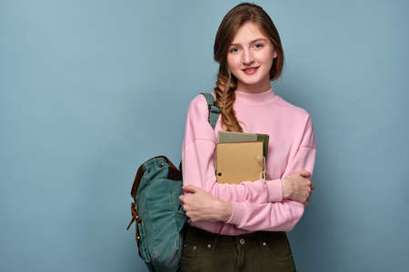 A blue-eyed girl in a pink sweater stands on a blue background with a backpack and books in her hands. Stock Photo