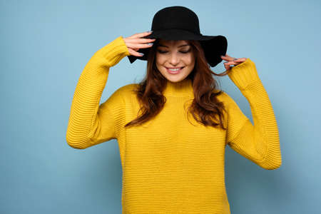 Beautiful brunette in a yellow sweater and stands on a blue background, straightening her black hat and closing her eyes, smiling.