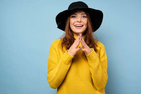 A beautiful brunette in a yellow sweater and black hat stands on a blue background, smiles, her fingers joined in front of her