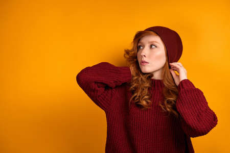 A curly red-haired girl in a burgundy sweater and hat stands on an orange background, straightening her hat, looks to the side.