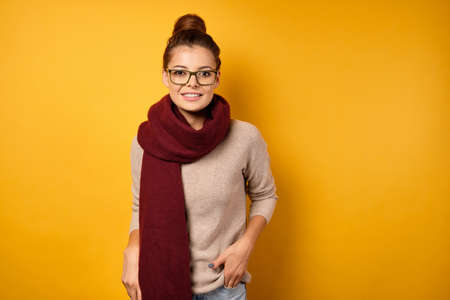 A beautiful brunette with gathered hair in a burgundy scarf and glasses stands on a yellow background and looks into the frame.