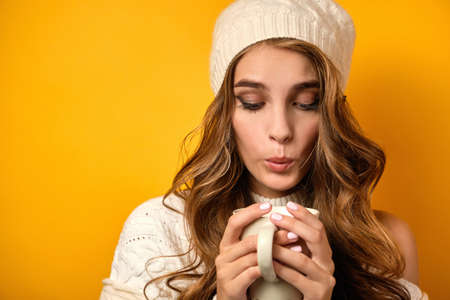 Portrait of a girl in a white sweater and hat on a yellow background, blowing into a mug in her hands, focus on her face. Zdjęcie Seryjne