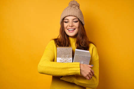 Beautiful brunette in a yellow sweater and stands on a yellow background with gift boxes in an embrace and smiling looking down. Zdjęcie Seryjne