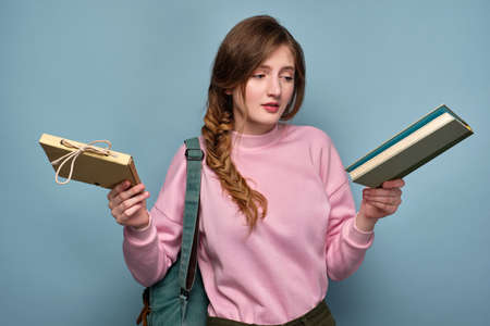 A girl in a pink sweatshirt with a braid stands on a blue background with a backpack and looks at bewildered books in her hands.