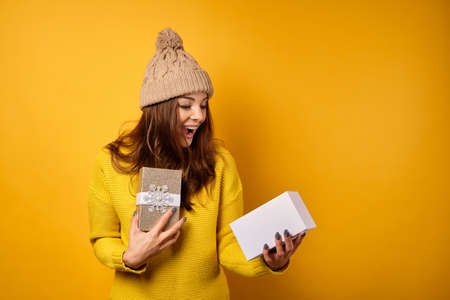 A beautiful brunette in a yellow sweater and hat stands on a yellow background with joyful looks inside an open gift box.