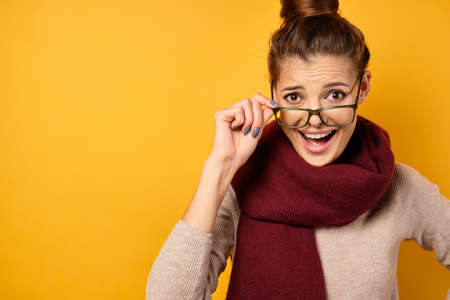 A beautiful brunette with gathered hair in a burgundy scarf looks with surprise in the frame with her glasses down. Zdjęcie Seryjne