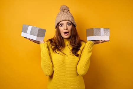 A beautiful brunette in a yellow sweater and hat stands on a yellow background with gift boxes on palms and looks in shocked frame