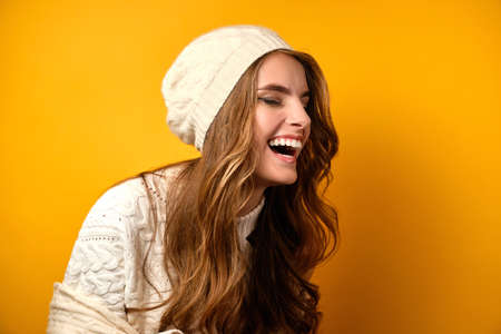 Portrait of a laughing girl in a white sweater and hat standing half-turn on a yellow background. Zdjęcie Seryjne
