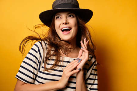 A beautiful brunette in a striped T-shirt and wicker hat is smiling on a yellow background, looking to the top with flying hair