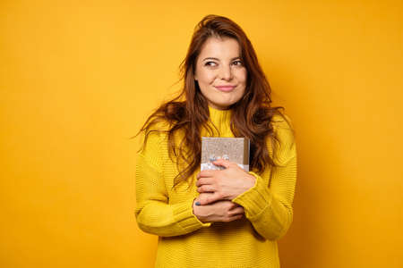 A beautiful brunette in a yellow sweater and stands on a yellow background clutching a gift box and looks cunningly to the side. Zdjęcie Seryjne