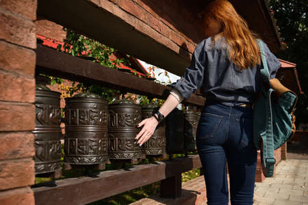 Red-haired girl stands in the sunshine, holding her hand on the prayer wheel of Mani