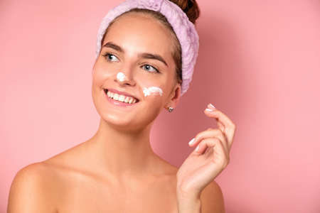 A beautiful girl with a bandage on her head a pink background smiles with smears of cream on her face Zdjęcie Seryjne