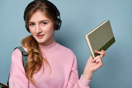 A blue-eyed girl with a backpack and in headphones holds a green book on a blue background.