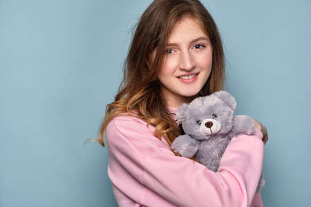 Blue-eyed girl cuddles with a toy gray bear standing on a blue background.