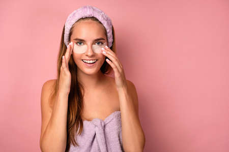 Portrait of a girl in a lilac towel correcting patches under her eyes and looking at the camera on a pink background.
