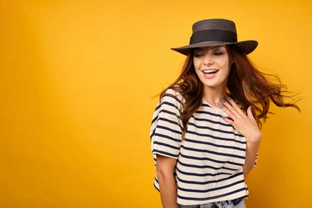A beautiful brunette in a striped T-shirt and wicker hat is standing smiling on a yellow background with flying hair.