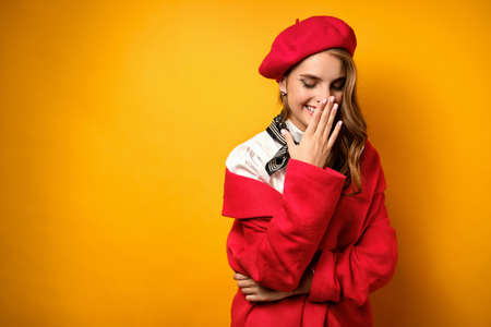 Portrait of a beautiful laughing blonde with red lipstick, in a white blouse, red coat and beret on a yellow background.