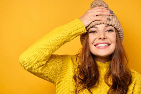 A beautiful brunette in a yellow sweater and hat stands on a yellow background, smiling broadly, with her hand on her forehead Zdjęcie Seryjne