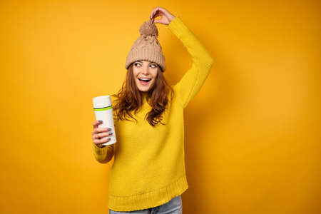 A beautiful brunette in a yellow sweater pulls the hat up by the pompom and looks to the side, holding a thermomug